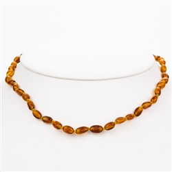 Lovely necklace composed of cognac colored amber.. Gold colored cord w/ knot between each bead. Perfect size for children over three. Definitely not intended for children 3 or younger due to the small parts and choking hazard.
