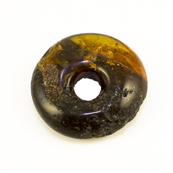 Very impressive polished doughnut shaped honey amber stone for pendant use. Weighs 9.7g. This amber stone is mainly polished but also has natural rough spots to highlight its natural origins.