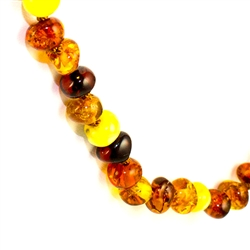 "Lovely necklace composed of cherry, custard, light and dark honey Amber. Oval Amber Bead size approx .2"" - .25"" diameter. Gold colored cord w/ knot between each bead. Gold claw clasp closure."