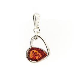 "A heart of silver filled on one side with an amber cabochon, ""Amber And  Love"" stamped on the side and a clear crystal imbedded in the side."