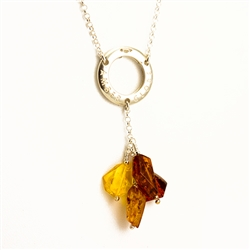 "This beautiful amber necklace features a silver circle stamped ""Amber Globe"" from which four amber stones are suspended."