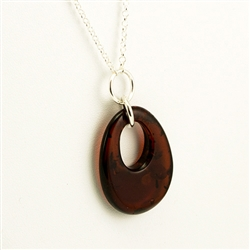 "This beautiful oval of amber hangs on a long 34"" sterling silver chain."
