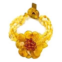 "Bozena Przytocka is a designer of artistic amber jewelry based in Gdansk, Poland. Here is a beautiful example of her ability to blend different shades and shapes of amber to create a stunning bracelet. Center amber flower is 1.5"" - 4cm in diameter.  4 st"
