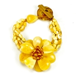 "Bozena Przytocka is a designer of artistic amber jewelry based in Gdansk, Poland. Here is a beautiful example of her ability to blend different shades and shapes of amber to create a stunning bracelet. Center amber flower is 1.5"" - 4cm in diameter. 4"