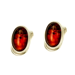 Beautiful pair of oval shaped cognac colored amber clip on earrings set in sterling silver.