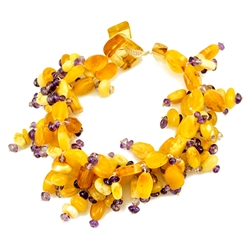 Amber and amethyst beaded strings woven together. Securely closes around your wrist with an amber toggle clasp. Amber is soft, only slightly harder than talc, and should be treated with care.