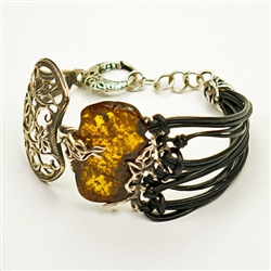 "Antiqued silver highlights this beautiful amber centerpiece (1.25"" x 1"" x .2"" - 3cm x 2.5cm x .5cm). Silver and black leather strands fits a wrist up to 8"" - 20cm diameter (adjustable)."