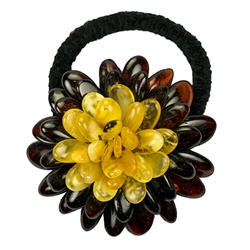 "This amber ""flower"" is compose of multiple polished beads sewn together with a knitted back. Attached with a stretch band."