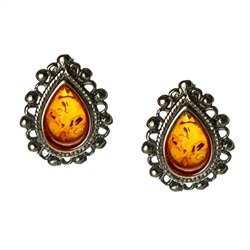 Artistic tear drop shaped silver earrings with a center of honey colored amber.
