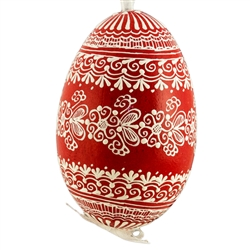This beautifully designed egg is dyed one color, then white wax is melted and applied to form an intricate design which is left on the surfce. The egg is emptied and strung with ribbon for hanging.