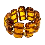 Delightful slices of natural amber connected  by a double strand of of woven stretch material and separated with beads. Rings start at size 5 and stretch to fit the largest fingers.