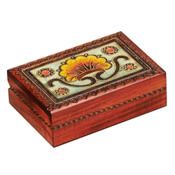 The lid of this box is decorated with a bright floral motif. A burned design around the edges of the lid and on the sides of the box completes the piece. The box is handmade in the Tatra Mountain region of Poland