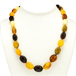 "Natural Baltic Amber Cherry, Custard, Light and Dark Honey Amber Oval Amber Beads  Graduated sizes up to .75"" long by .6"" wide bronze colored cord w/ knot between each bead. Silver claw clasp closure."