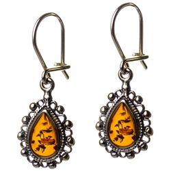 "Artistic antique tear drop shaped silver earrings with a center of honey colored amber. Approx 1"" long."