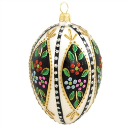 "Add a glistening addition to your holiday décor with this beautiful egg! Crafted of glass in Poland and painted a cream white, this 4"" egg is accentuated with vibrant green, black and gold glazes, and dazzling gold, green, red, silver, blue and pink"