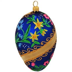 "Our elegant egg ornament features gold swirls on a matte blue finish. Crafted of glass accentuated with beautiful flowers lavishly coated in dazzling glitter, this 3¾"" tall unique egg will make the perfect addition to any holiday décor!"