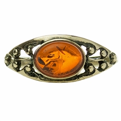 "A small oval of honey amber set in a classic sterling silver setting. Size approx .25"" x .4"""
