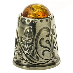 "A beautifully designed silver thimble topped with amber.  Size approx 1"" x .75""."