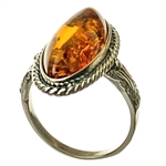 "A beautiful oval of cognac colored amber set in sterling silver.   Size approx .75"" x .5""."
