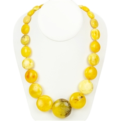 This beautiful beaded amber necklace features rounded disc shaped Baltic custard amber strung together and finished with an amber closure. The beads are knotted between each bead.