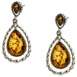 "Artistic antique oval shaped silver earrings with a center of honey colored amber. Approx 1"" long."
