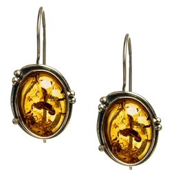"Artistic antique oval shaped silver earrings with a center of honey colored amber. Size approx 1.25"" x .6""."