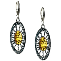 Artistic antique oval shaped silver earrings with a center of honey colored amber.