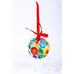 "Folk art is the perfect souvenir from Poland. This ornament is inspired by the paper cuts from the Lowicz area of central Poland.  Lightweight, unbreakable plastic with a decorative Lowicz pattern. Comes with a red ribbon for handing. Size approx 3"" dia"