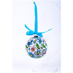 Folk art is the perfect souvenir from Poland. This ornament is inspired by the flower designs from the Kashub area of northwest Poland. Lightweight, unbreakable plastic with a decorative Kashub floral pattern. Comes with a green ribbon for handing. Size a
