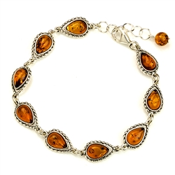 "9 tear shaped amber beads each set in an antique style sterling silver frame. 7"" - 18cm long."