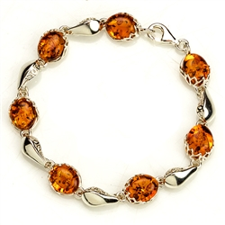 "7 oval amber beads each set in a sparkling sterling silver frame. 7"" - 18cm long."