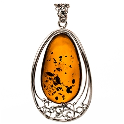 Sterling Silver with filigree detail surrounding a beautiful honey amber cabochon.