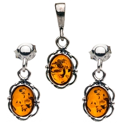 "Petite Baltic Amber oval stud earrings and pendant set surrounded with a ring of Sterling Silver filigree work. Approx .75"" long x .375"" wide."