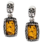 "Gorgeous Baltic Amber stud earrings surrounded with a ring of antique style sterling silver. Size approx .75"" x ..375."