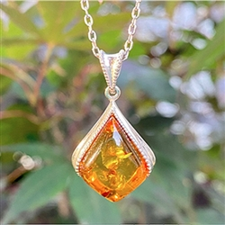 "Sterling Silver with antique detail framing a beautiful honey amber cabochon.  Amber cabochon is approx 1"" x .75""."