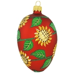 "Bringing to mind the bountiful blooms of summer, this resplendent glass egg is decorated with a garden of vivid yellow sunflowers and verdant green leaves. Shimmering with a beautiful red matte surface, this egg-quisite ornament measures 3½"" tall and is m"