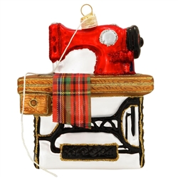 "Sew charming is our sewing machine ornament! Measuring 4.5"" tall, our nostalgic ornament features the vintage sewing machine of yesteryear with a piece of plaid ribbon draping down and a dangling crème thread wrapped around the topper. Crafted in Poland"