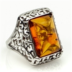 "Honey colored amber and sterling silver filigree ring. Size approx. .5"" x .75""."
