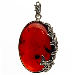 "Beautiful cherry amber cabochon framed in antique style sterling silver.  Please note that this picture was taken with background light to highlight the interior.  Actual appearance is dark cherry. Size is approx 2.25"" x 1.25"" x .5""."
