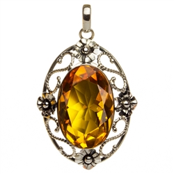 "Sterling Silver with filigree detail surrounding a beautiful diamond cut honey amber cabochon.  Size is approx 2.2"" x .1.4"" x .5""."