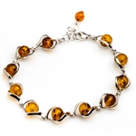 "11 round amber beads each framed in sterling silver. 8.5"" - 22cm long."