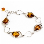 "4 tear drop shaped amber beads each set in a sterling silver frame. Size is 7.5"" diameter with a 1"" extender."