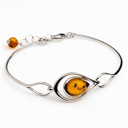 "This sterling silver bracelet features a gorgeous center of honey amber.  Size is 7"" with a 1"" extender."