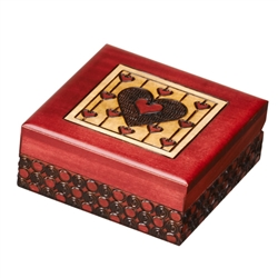 This box is decorated with multiple hearts on the lid and circular detailing around the sides. Finished a red stain.