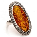 "Honey colored amber and sterling silver oval ring. ​Size approx. 1.5"" x .9"".​"