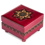 This puzzle box features an abstract, symmetrical design on the lid, with a fuchsia finish. The trick to opening this box is to turn the rotating leg on the bottom.