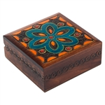 This square brown box has a turquoise flower on its lid, along with other accent designs. A swirling border runs along the sides of the box.