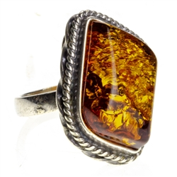 "Honey colored amber and sterling silver  ring. Size approx. 1"" x .75""."