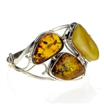 "This sterling silver bracelet features a gorgeous cluster of mixed amber colors. Bracelet Size is 7"" diameter.  Cabochon cluster measures approx 1.5"" x 2""."
