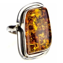 "Honey colored amber cabochon framed in sterling. Size approx. 1"" x .75""."